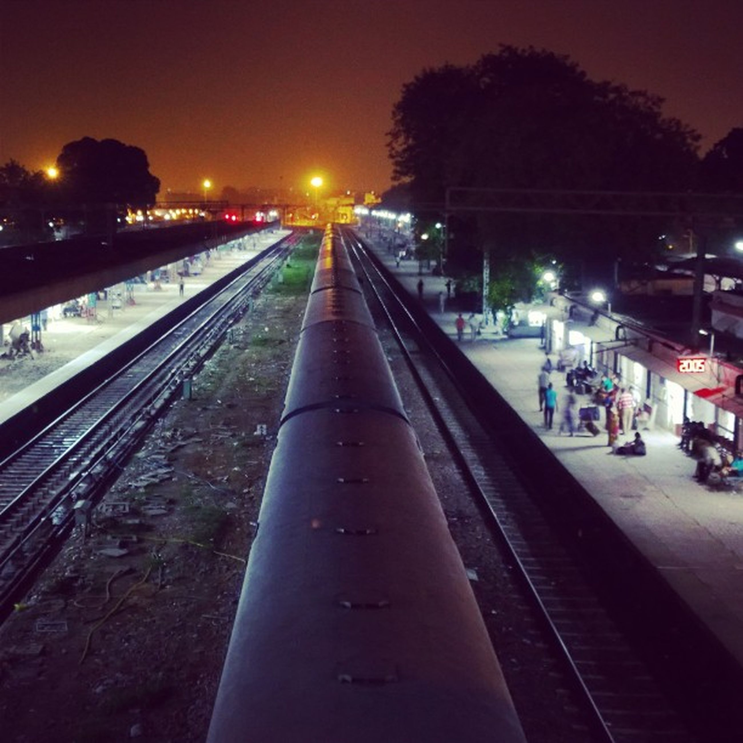 illuminated, transportation, night, railroad track, street light, the way forward, diminishing perspective, city, railroad station platform, public transportation, lighting equipment, rail transportation, vanishing point, railroad station, mode of transport, building exterior, high angle view, road, built structure, travel