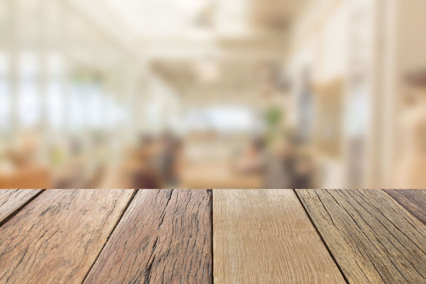 Empty wooden table top perspective with blur coffee shop background, used for montage or display your products. Close-up Day Focus On Foreground Indoors  Montage No People Wood - Material Wooden