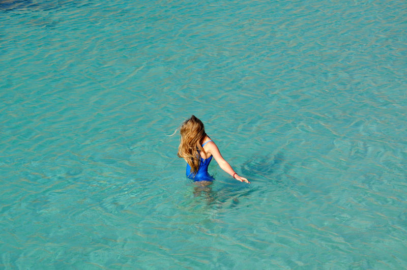High Angle View Of Girl Swimming In Sea
