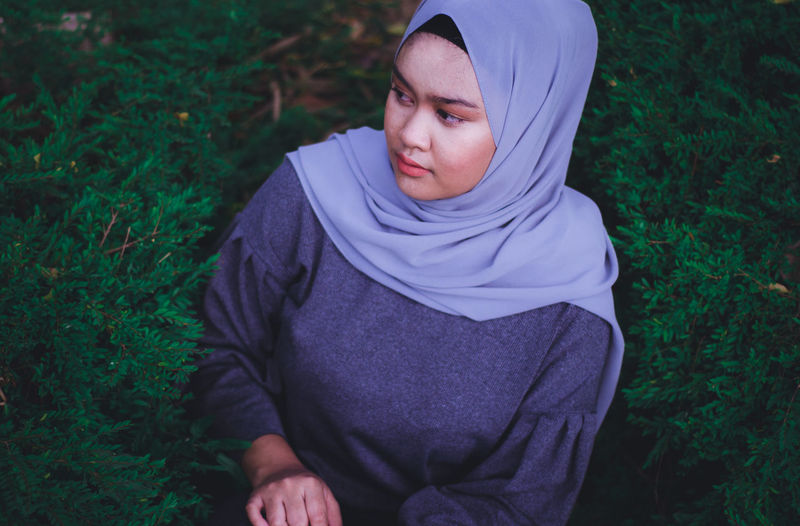 High Angle View Of Young Woman In Hijab Standing On Field