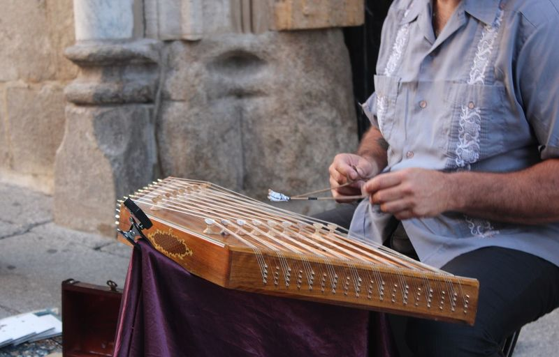 Midsection of street musician playing santur on footpath