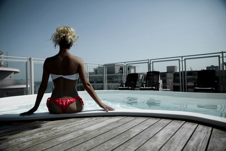 Rear view of beautiful woman sitting at poolside on building terrace against clear sky