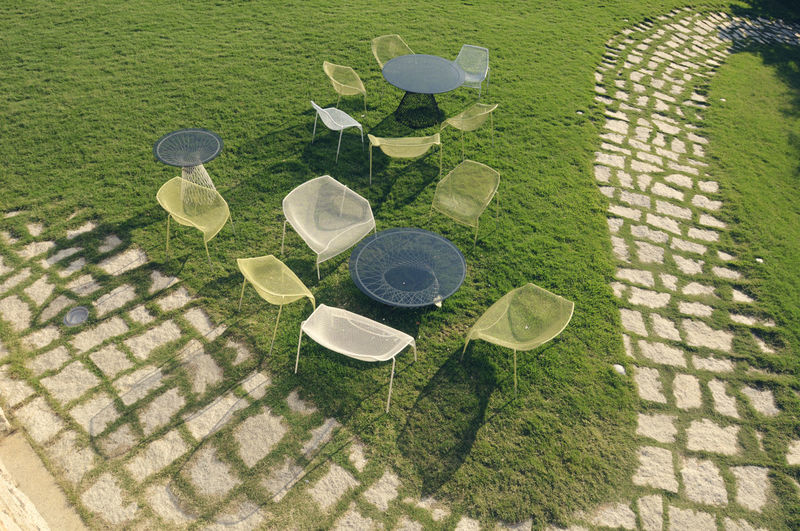 High angle view of tables and chairs in lawn during sunny day