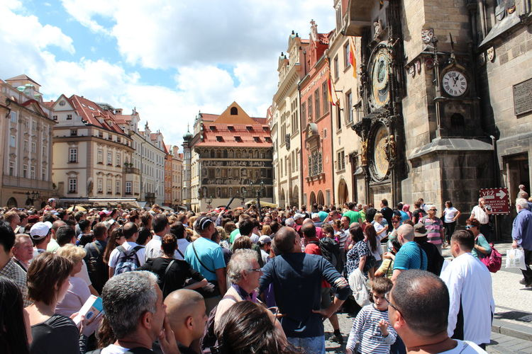 Crowd at town square standing by prague astronomical clock against sky