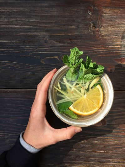 Human Hand Human Body Part Healthy Eating Food And Drink Holding One Person Freshness Healthy Lifestyle Food Table High Angle View Directly Above Wood - Material Indoors  One Woman Only Citrus Fruit Only Women People Day Tea Time tea Tea Asian Tea Berlin Lunch Time! Minze
