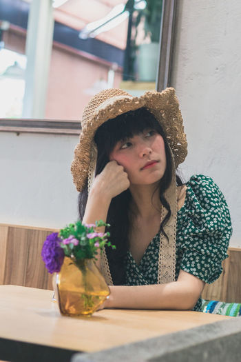 Thoughtful young woman sitting in restaurant