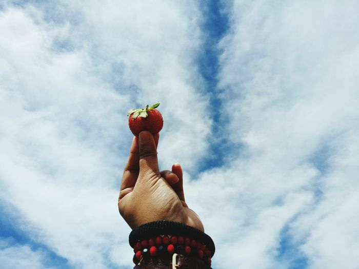 Cropped hand holding strawberry against cloudy sky