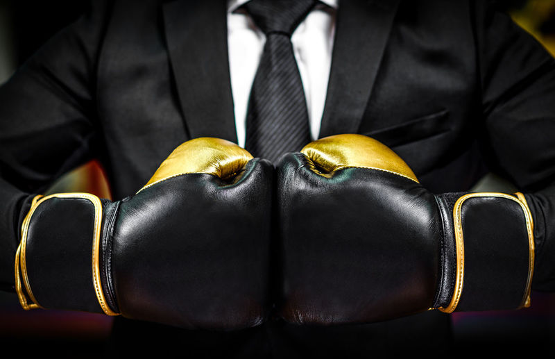 Close-Up Of Midsection Of Businessman Wearing Boxing Glove