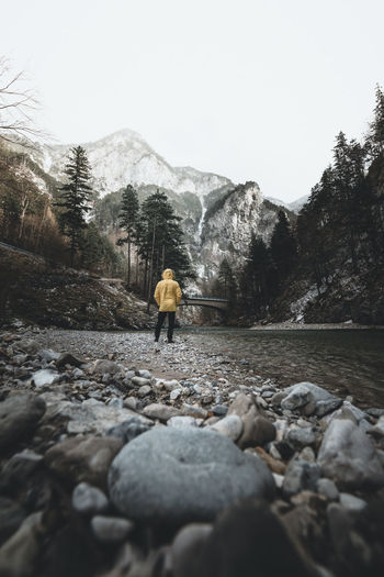 Rear view of man standing at riverbank in forest against snowcapped mountains