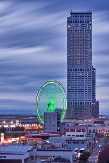 Illuminated ferris wheel in city against sky at dusk