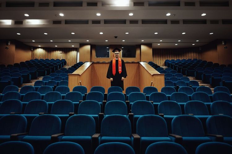 Man standing amidst chair in lecture hall