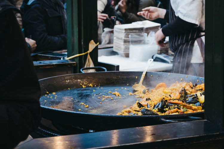 Large pan of paella at a street food market, unidentifiable people on the background.