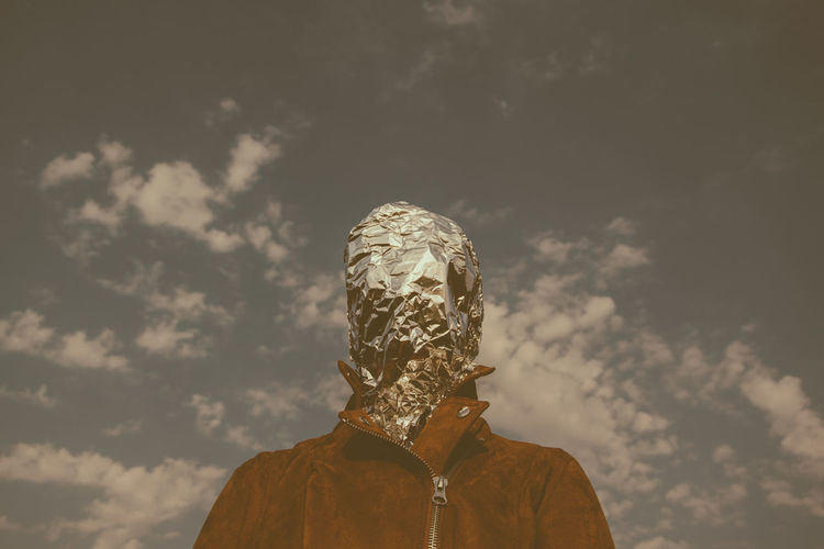 Man with face covered in foil standing against sky