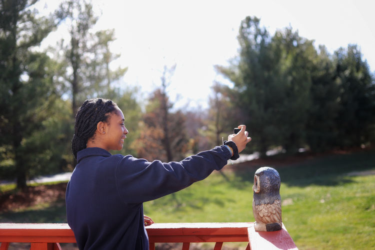 Side view of young woman  taking a selfie