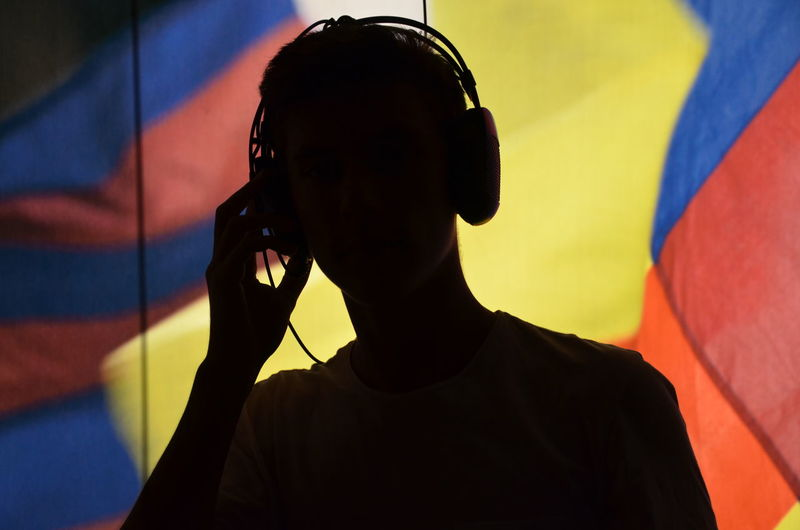 Close-up of silhouette man holding headphones