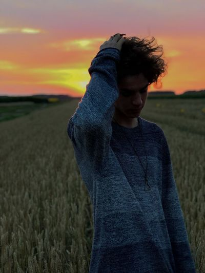 Teenage boy with hand in hair standing on land against sky during sunset