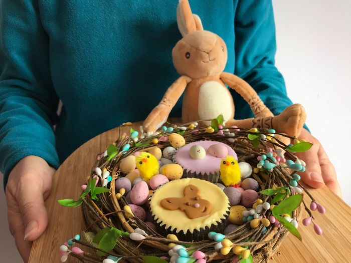 Woman holding  bamboo board with iced cupcakes and chocolate easter eggs in a decorative nest shape.