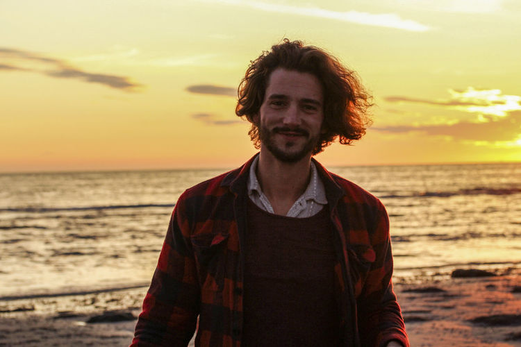 Portrait of smiling young man standing at beach against sky during sunset