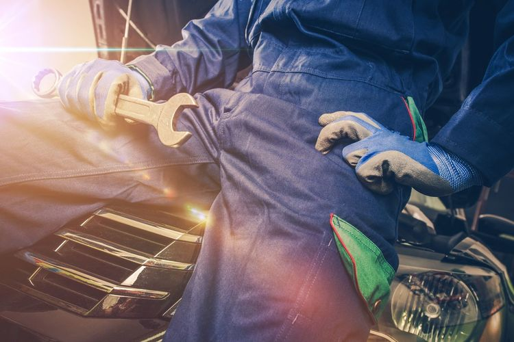 Midsection Of Mechanic Holding Wrench While Sitting On Car At Auto Repair Shop
