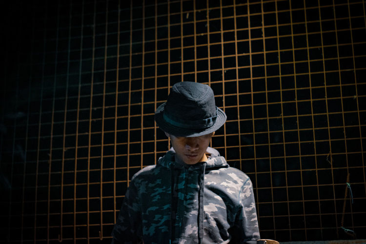 Man wearing hat while standing against fence