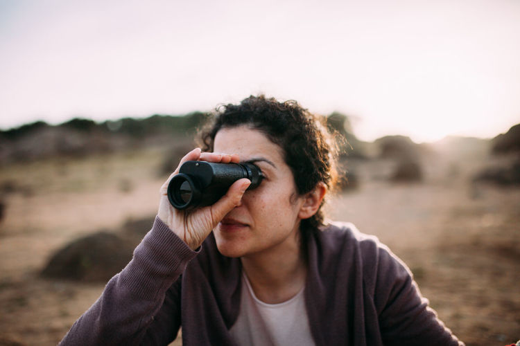 Woman looking through binocular on field