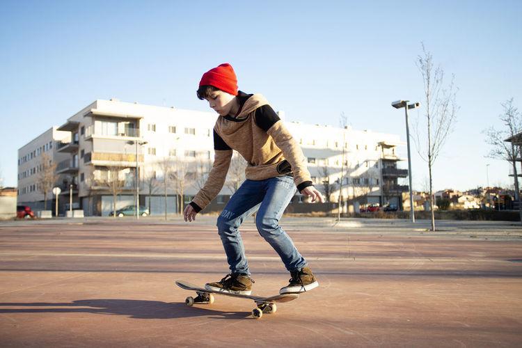 Full length of man skateboarding on street in city
