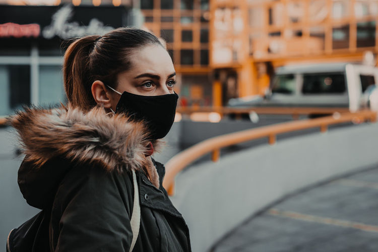 Young woman wearing mask looking away while standing in city