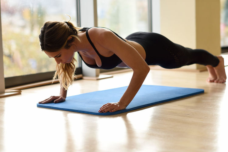 Young beautiful woman doing pushups in the gym on blue mat. Girl wearing sportwears clothes. Balance Concentration Day Exercising Flexibility Full Length Gym Healthy Lifestyle Indoors  Indoors  Lifestyles One Person People Push Ups Pushups Real People Self Improvement Sports Clothing Strength Wellbeing Yoga Young Adult Young Women