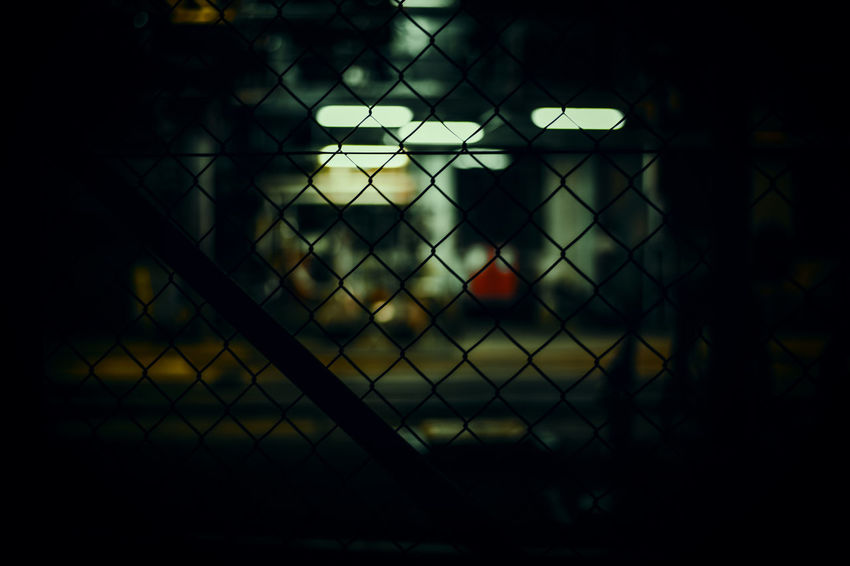 Tried myself in streetphotography. More to follow Artificial Light Dark Security Chainlink Fence Close-up darkness and light Fence Focus On Foreground Neon Lights Night Safety Street Photography Streetphotography
