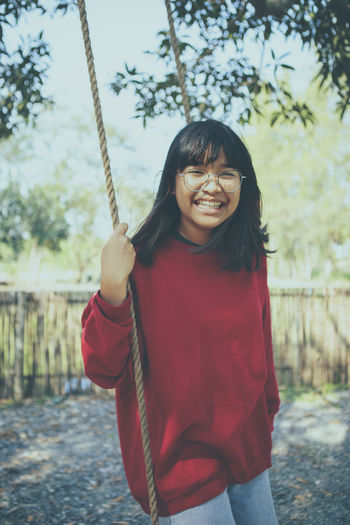 Asian teenager toothy smiling with happiness in park