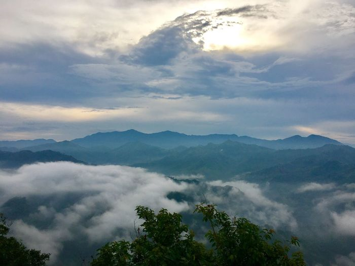 Scenic view of foggy mountains against sky