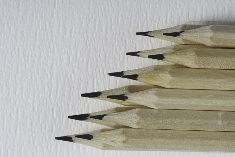 Close-up of colored pencils on table against wall