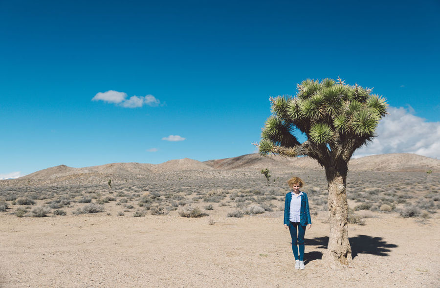 Arid Climate Arid Landscape Blue Blue Sky Curly Hair Day Death Valley Death Valley National Park Desert Desert Full Length Girl Joshua Tree Landscape Mountains Nature Nature One Person Outdoors Real People Rear View Roadtrip Sand Tranquil Scene Walking