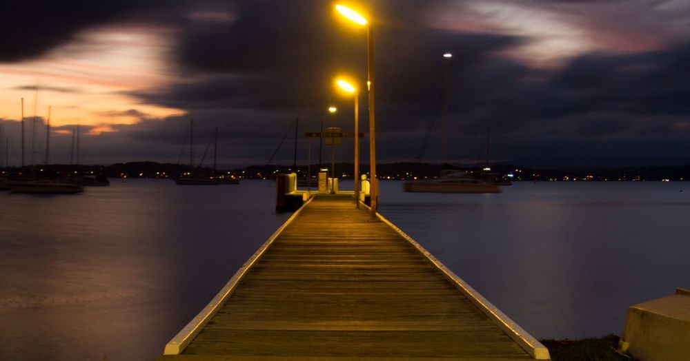 Pier on sea lit up at night