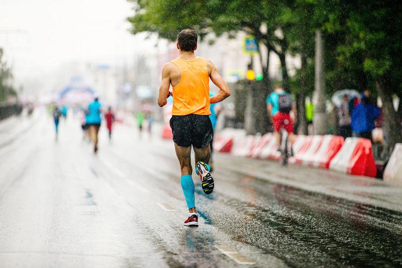 Back runner athlete run in rain on road city marathon