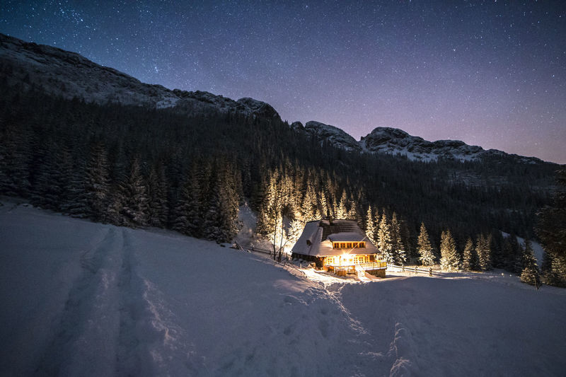 Illuminated house on snow covered landscape at night