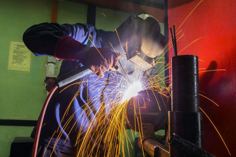 Welder working in auto repair shop