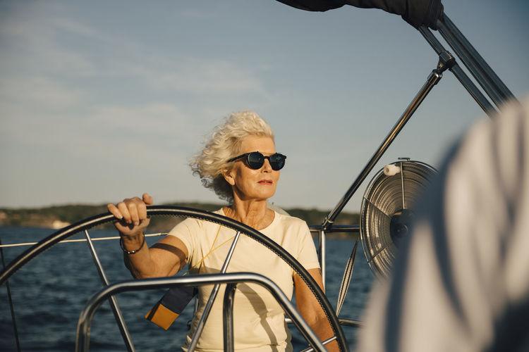 Man wearing sunglasses against boat in sea against sky