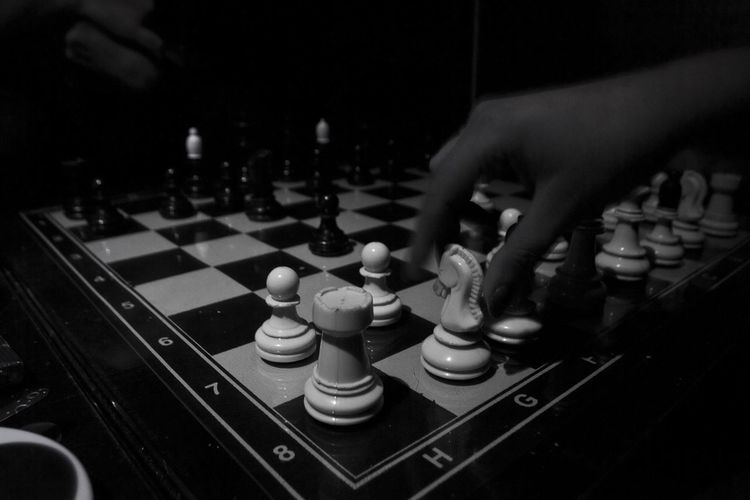 Cropped hand playing chess in darkroom