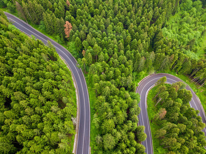 Winding road through the forest, from high mountain pass, in summer time. aerial view by drone
