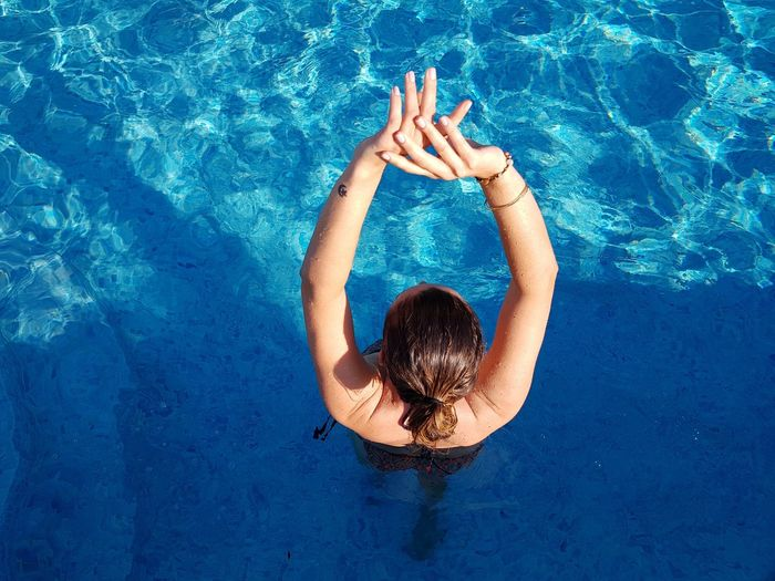 High angle view of woman standing in swimming pool