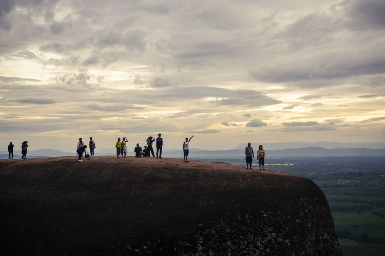 People standing on rock against sky during sunset
