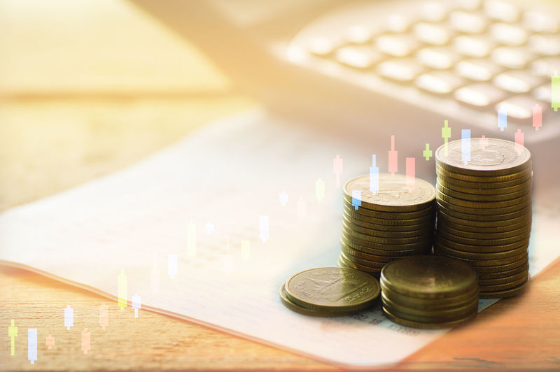 Digital composite image of coins and forex chart on desk