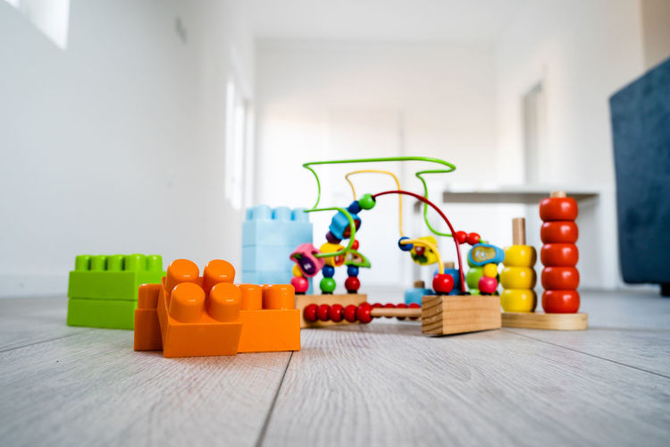 Indoors  Toy Multi Colored Wood - Material Still Life No People Table Home Interior Selective Focus Toy Block Focus On Foreground Lifestyles Flooring Domestic Room Plastic Group Of Objects Close-up In A Row Orange Color