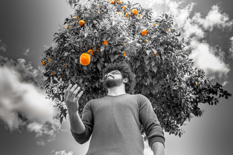 The falling orange Blackandwhite Clouds And Sky Falling Falling Fruit Long Leaves Only Orange Orange Tree Saturation Sky Standing Young Adult Young Men
