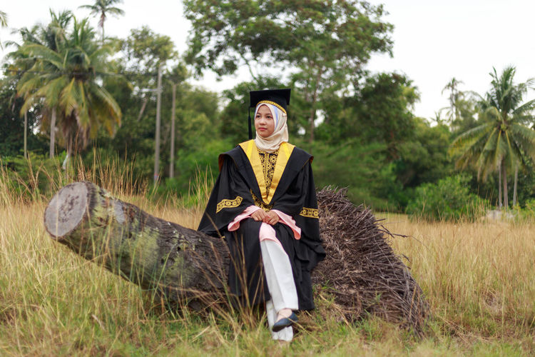 Woman In Graduation Gown Sitting On Log