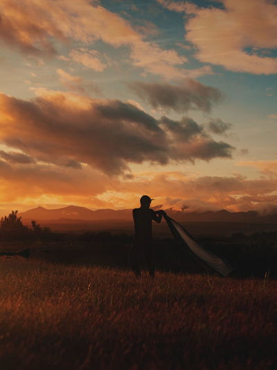Man working on field against sky during sunset