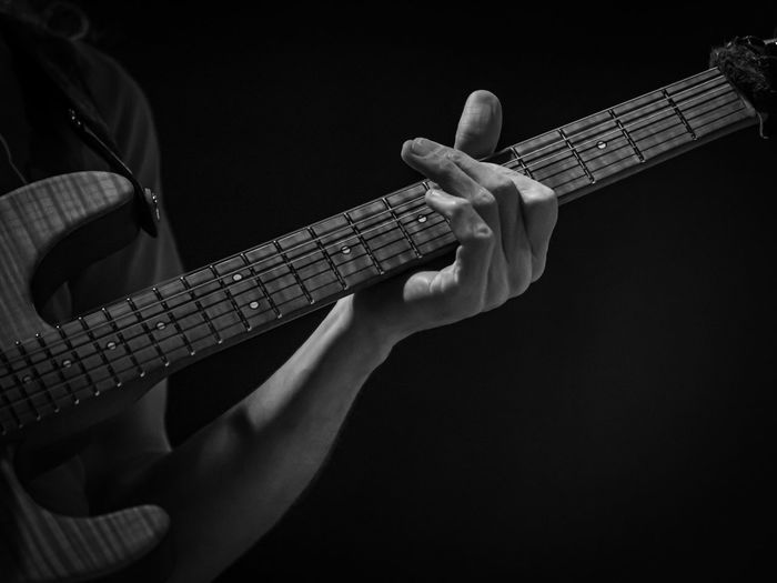 Man playing guitar against black background