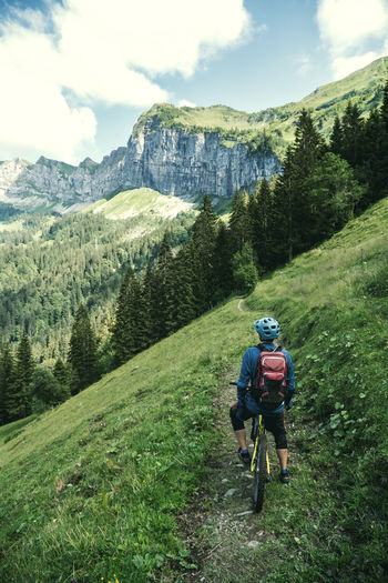 Rear view of man on his mountain bike enjoying the view in the swiss alps.
