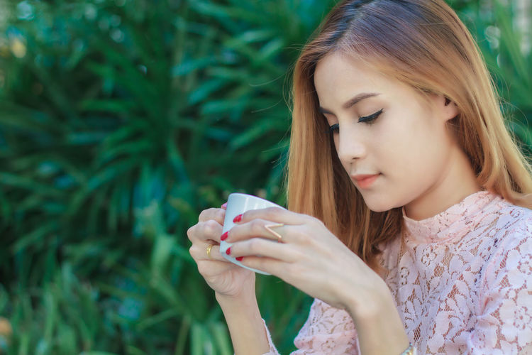 Young woman holding coffee cup against plants